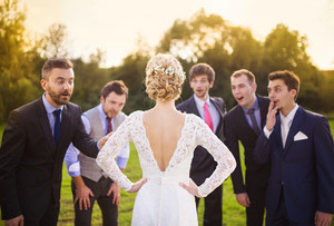 Portrait of surprised groomsmen looking at beautiful bride outside