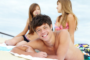 Portrait of teenage guy lying on the beach and sunbathing with two girls behind