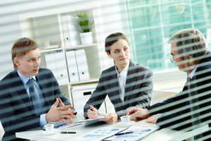 Portrait of three business people sharing ideas at meeting in office