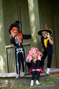 Portrait of three Halloween girls looking at camera on the porch of dilapidated house