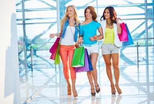 Portrait of three pretty shoppers walking down trade center