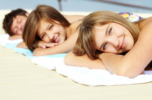 Portrait of three teenage friends lying on the beach and sunbathing