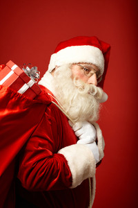 Portrait of tired Santa Claus carrying big red sack with gifts