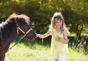 Portrait of tlittle girl having fun at countryside outdoors, feeding pony