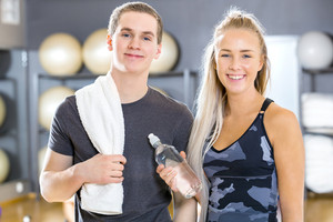 Portrait of two cheerful people having a break at gym