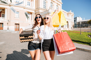 Portrait of two female friends shopping together and walking with colourful bags