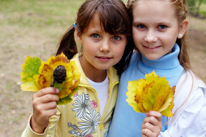Portrait of two girls holding yellow leaves and looking at camera with smiles