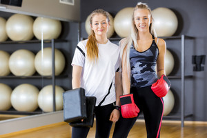 Portrait of two women at boxing training in fitness gym