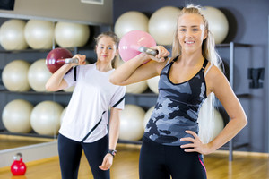 Portrait of two women with kettlebells at fitness gym