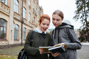 Portrait of two young female students reading book outside at the university campus