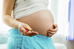 Portrait of unrecognizable pregnant holding pills in her hands