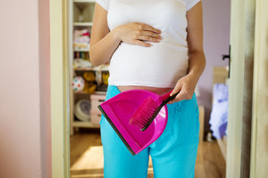 Portrait of unrecognizable pregnant woman holding dustpan and broom, cleaning home