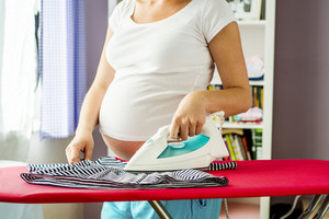 Portrait of unrecognizable pregnant woman ironing her future baby's clothes