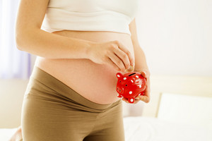 Portrait of unrecognizable pregnant woman measuring holding piggy bank in her hand