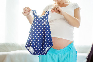 Portrait of unrecognizable pregnant woman with her future baby's clothes