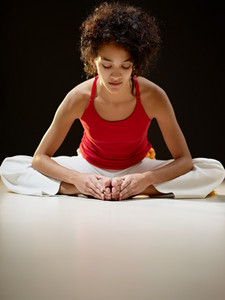 portrait of young adult latin american female sitting on white floor doing yoga exercise. Vertical shape, full length, front view, copy space