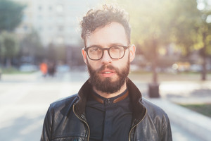 Portrait of young bearded caucasian man outdoor looking camera - customer, serious concept