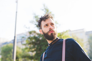 Portrait of young bearded caucasian man outdoor looking over pensive - customer, serious concept