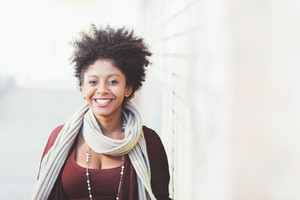 Portrait of young beautiful afro black woman looking at camera smiling - happiness, carefree, having fun concept