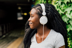 Portrait of young beautiful afro woman listening music with smart phone outdoor in the city - music, relaxing concept