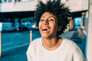 Portrait of young beautiful afro woman outdoor in the city back light having fun - carefree, serene, thoughtless concept