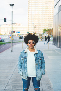 Portrait of young beautiful afro woman outdoor in the city having fun - carefree, serene, thoughtless concept