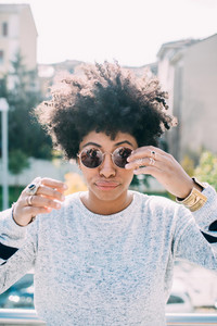Portrait of young beautiful afro woman outdoor in the city having fun wearing sunglasses - carefree, serene, thoughtless concept