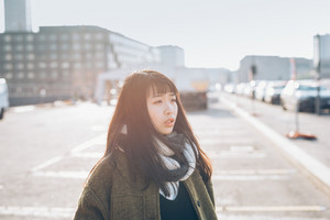 Portrait of young beautiful asian hipster woman outdoor in city back light, overlooking pensive - serious, thoughtful, thinking future concept concept