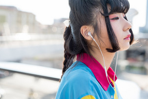 Portrait of young beautiful asian millennial woman listening music with earphones outdoor in city back light - relaxing, music, technology concept