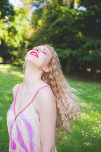 Portrait of young beautiful caucasian blonde hair woman outdoor in a city park laughing, moving her hair - beauty, hair care, happiness concept