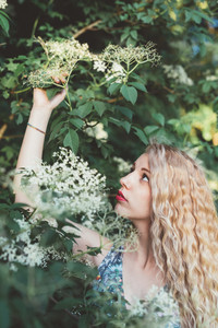 Portrait of young beautiful caucasian blonde hair woman outdoor in a city park picking flower serene - beauty, hair care, skin care concept