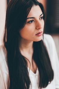 Portrait of young beautiful caucasian brown hair woman pensive - melancholic, serious, hair care concept