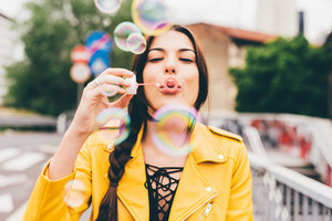 Portrait of young beautiful caucasian brown hair woman playing with bubblesoap - playful, carefree concept
