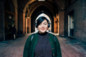 Portrait of young beautiful caucasian curvy woman outdoor in the city listneing music with headphones and eyes closed - relaxing, enjoying, technology concept