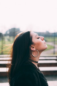 Portrait of young beautiful caucasian long brown hair woman with septum piercing feeling free outdoor in the city, eyes closed - freedom, relaxing, peaceful concept