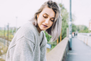 Portrait of young beautiful caucasian purple grey hair woman outdoor in the city looking over, smiling - happiness, carefree, serene concept