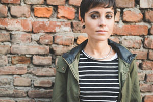 Portrait of young beautiful caucasian short hair woman looking in camera serious - pensive, thoughtful, melnacholic concept