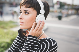 Portrait of young beautiful caucasian woman listening music with smart phone hand hold - relaxing, technology, music concept