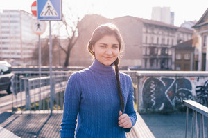 Portrait of young beautiful eastern woman in city back light looking in camera smiling - happiness, serene, customer concept