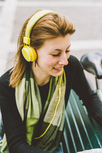 Portrait of young beautiful hipster sporty blonde woman in town listening music with headphones, smiling - relaxing, happiness, joy concept