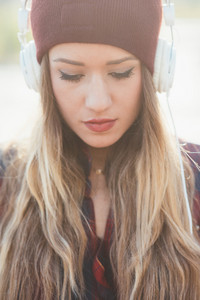 Portrait of young beautiful long blonde hair womam listening music with headphones, looking down serene - melancholic, music, relaxing concept