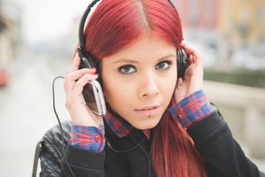 Portrait of young beautiful red hair venezuelan woman listening music with headpones and smart phone outdoor - music, relaxing, technology concept