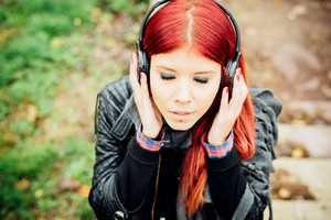 Portrait of young beautiful red hair venezuelan woman outdoor listening music with headphones and eyes closed - relaxing, music, technology concept