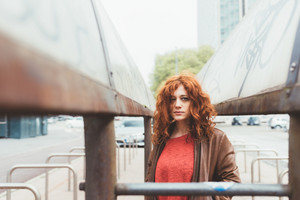 Portrait of young beautiful redhead woman outdoor overlooking melancholic - pensive, serious, customer concept