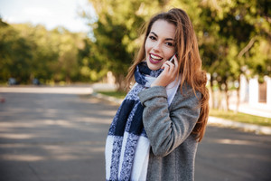 Portrait of young cheerful woman wearing scarf talking on cellphone against nature background. Looking at camera.
