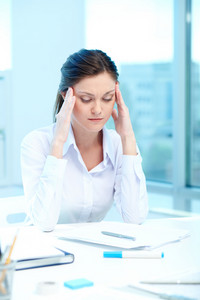 Portrait of young female touching her head while planning work