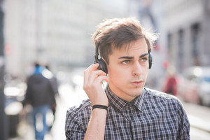 Portrait of young handsome alternative dark model man listening to music with headphones and smartphone connected wireless