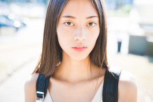 Portrait of young handsome asiatic long brown straight hair woman posing in the city backlight, looking in camera, pensive - serious, thoughtful, thinking future concept