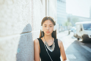 Portrait of young handsome asiatic woman posing in the city backlight looking in camera listening music with headphones - music, relaxing, pensive concept