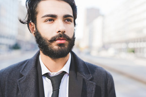 Portrait of young handsome caucasian bearded businessman posing outdoor in the street, overlooking pensive - business, thoughtful, serious concept